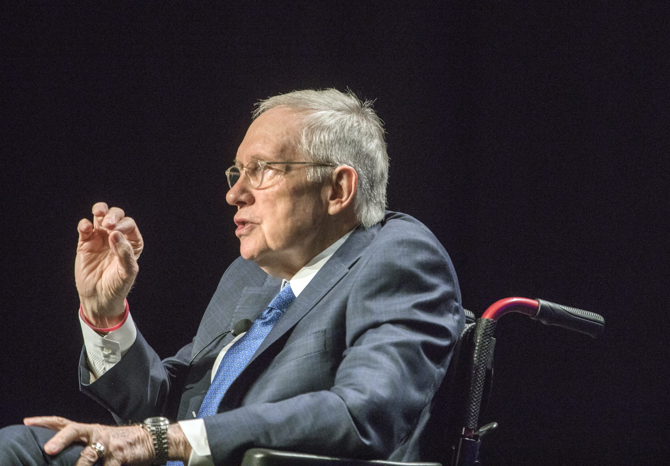 Harry Reid seated wearing a gray sportcoat and blue tie
