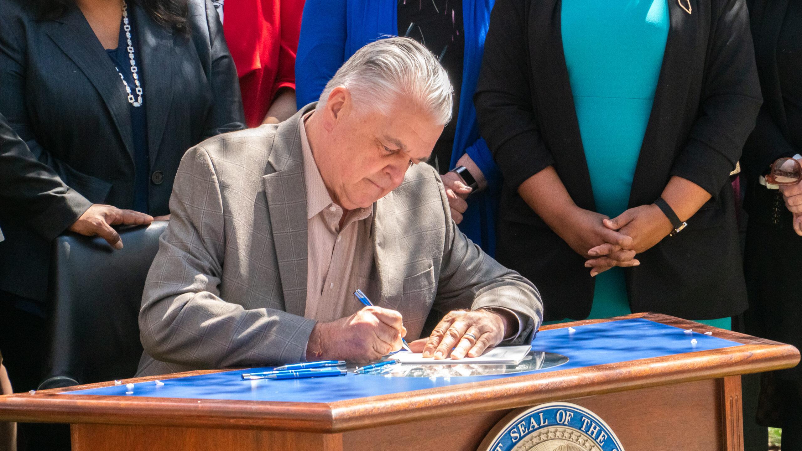 Gov. Sisolak signing SB358 on Earth Day outside of the legislature