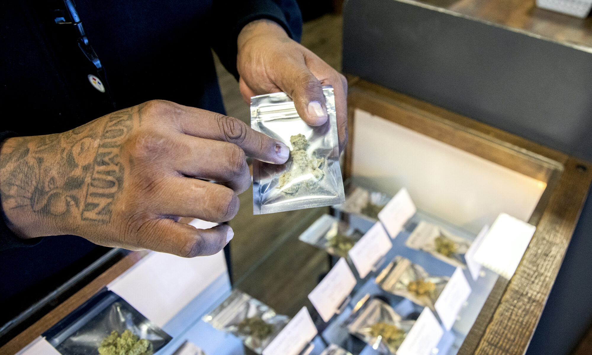 Man's hands holding and showing marijuana products above a sales counter