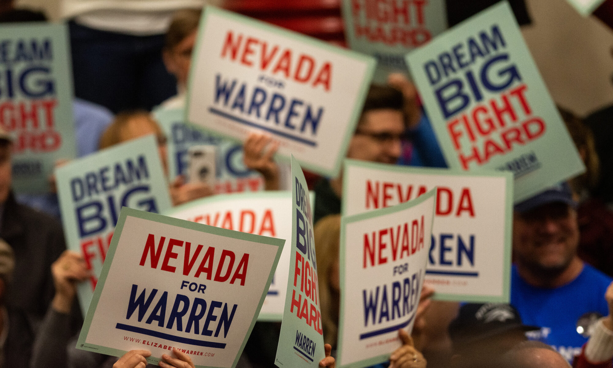 Signs being held up reading Nevada for Warren and Dream Big Fight Hard during a campaign rally