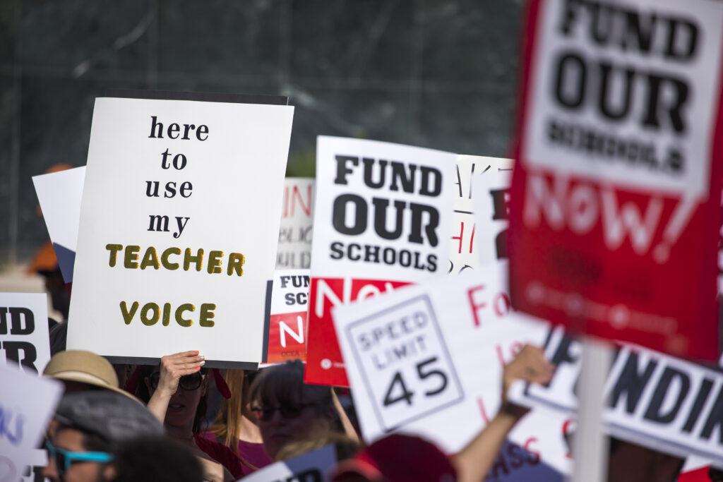 "Rally signs saying ""Fund Our Schools"""