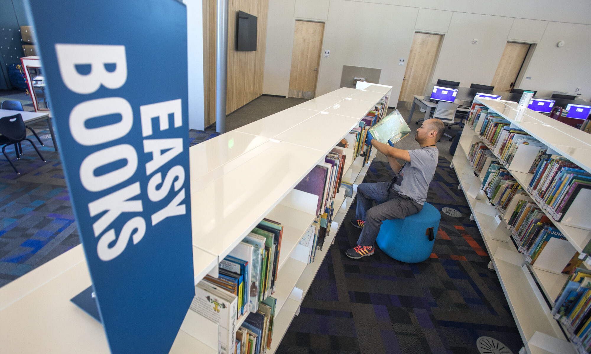 person shelving books in library