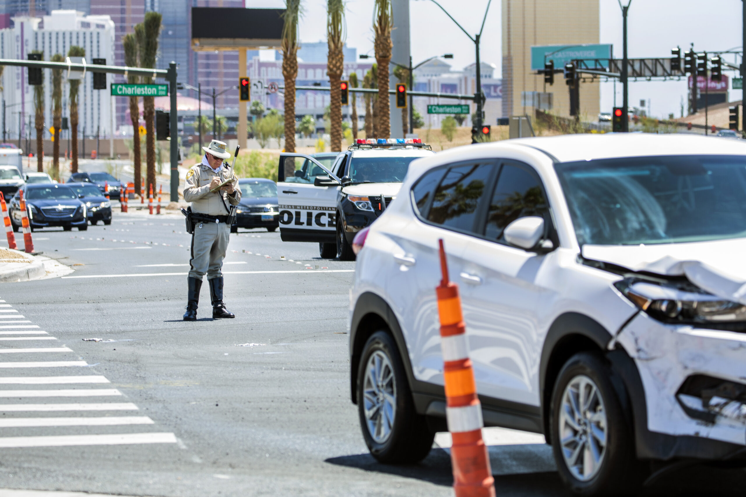 A police officer stands at the scene of a traffic accident.