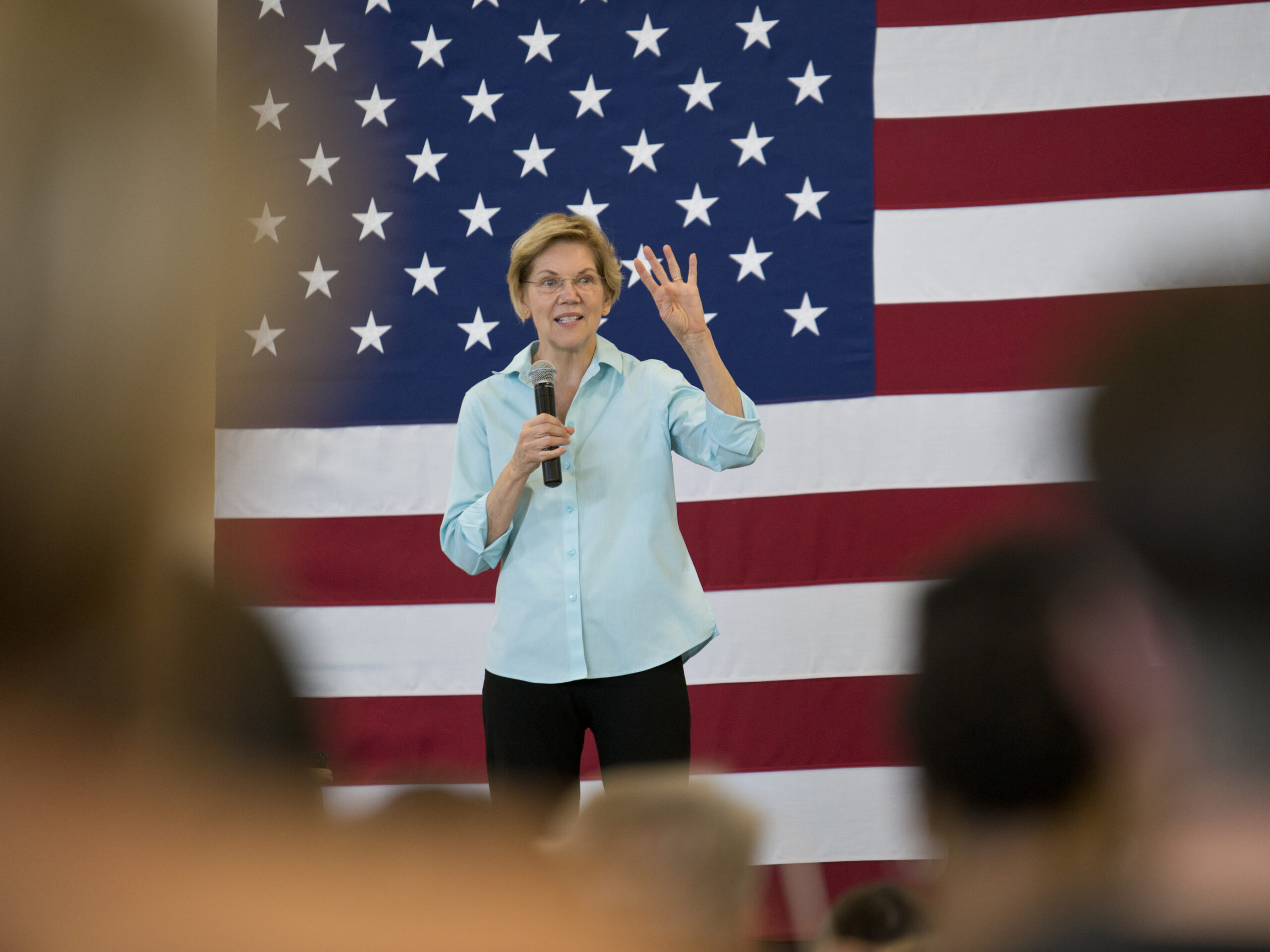 Massachusetts Senator Elizabeth Warren speaking to a crowd while standing in front of an American flag
