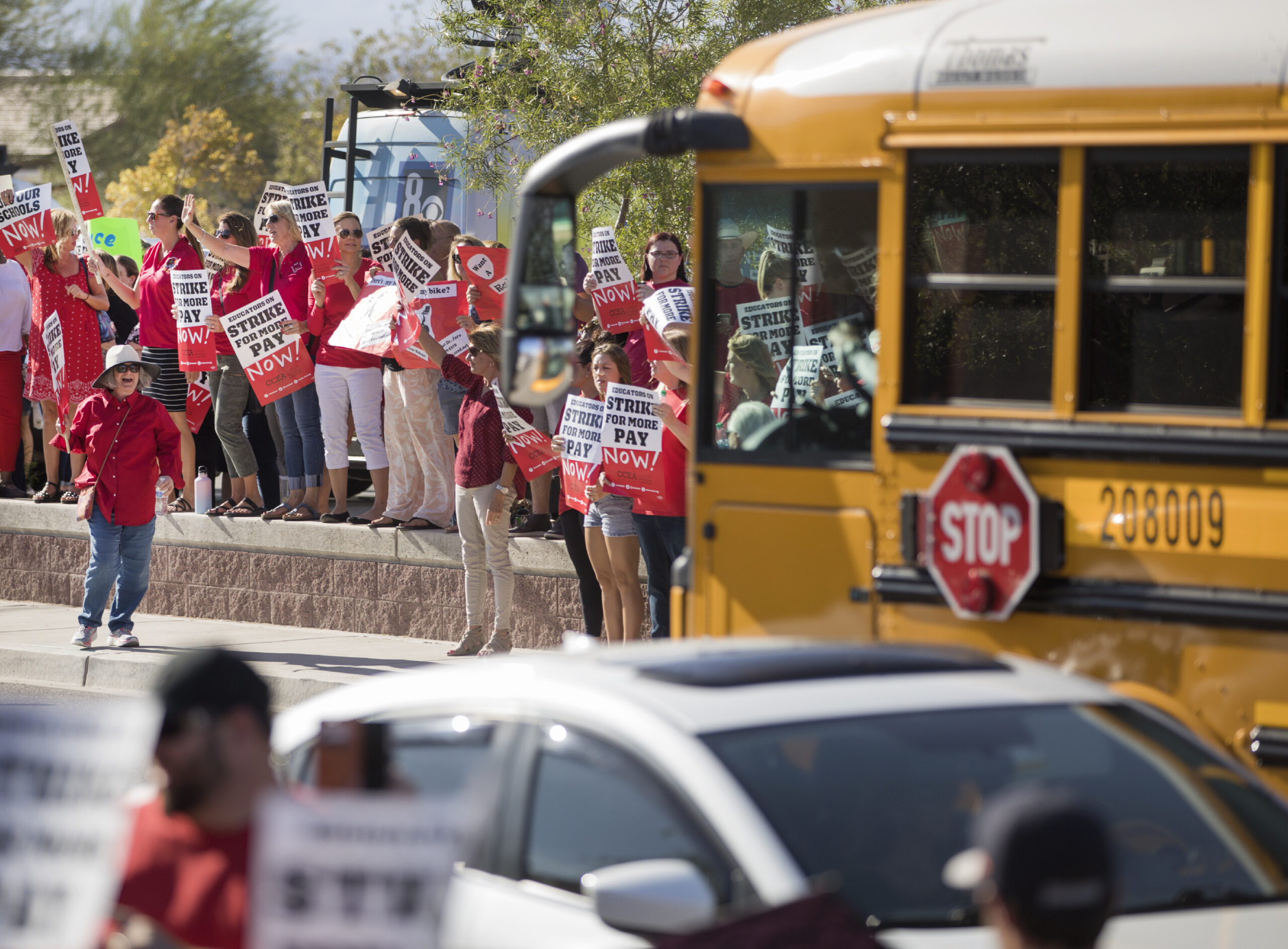 A school bus parked in front of a group of teachers wearing red shirts during a rally