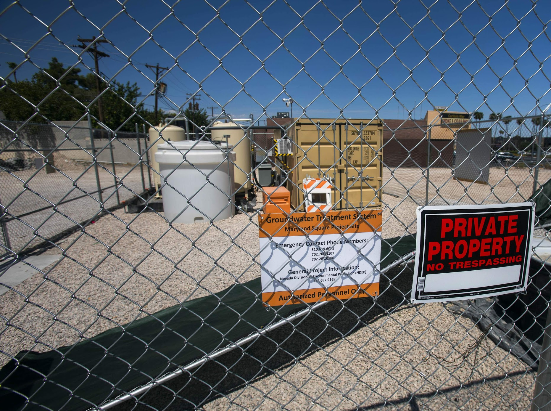A private property sign on a chain link fence in front of items at the former site of a dry cleaner in Maryland Square