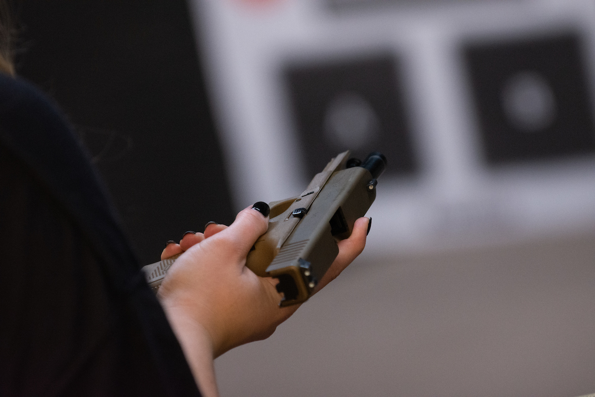 A handgun being held flat in a persons hands