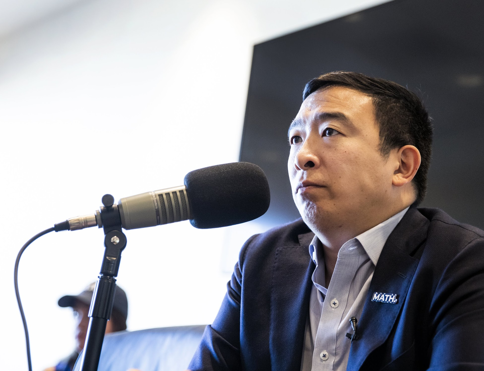 Andrew Yang speaks into a microphone