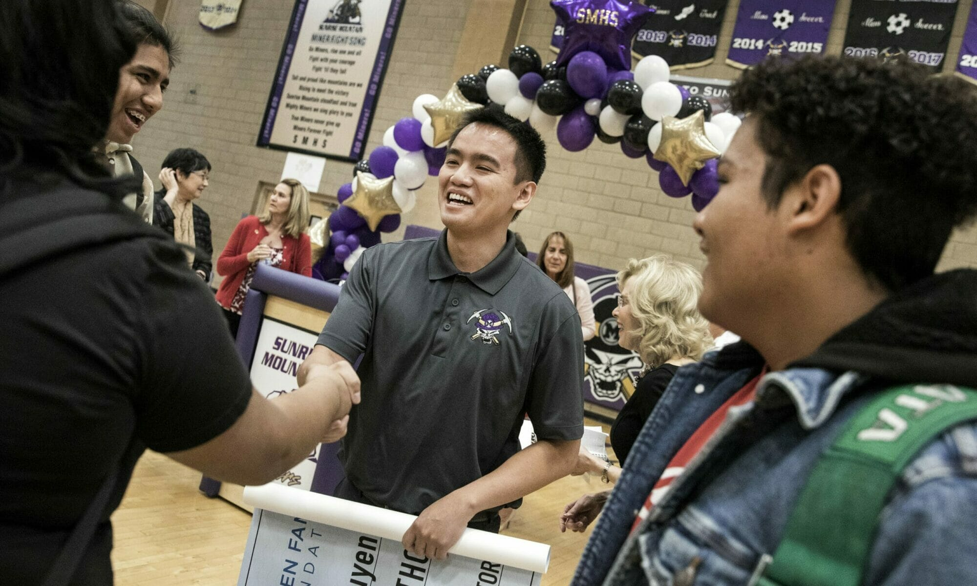 Ben Nguyen shaking hands with a student