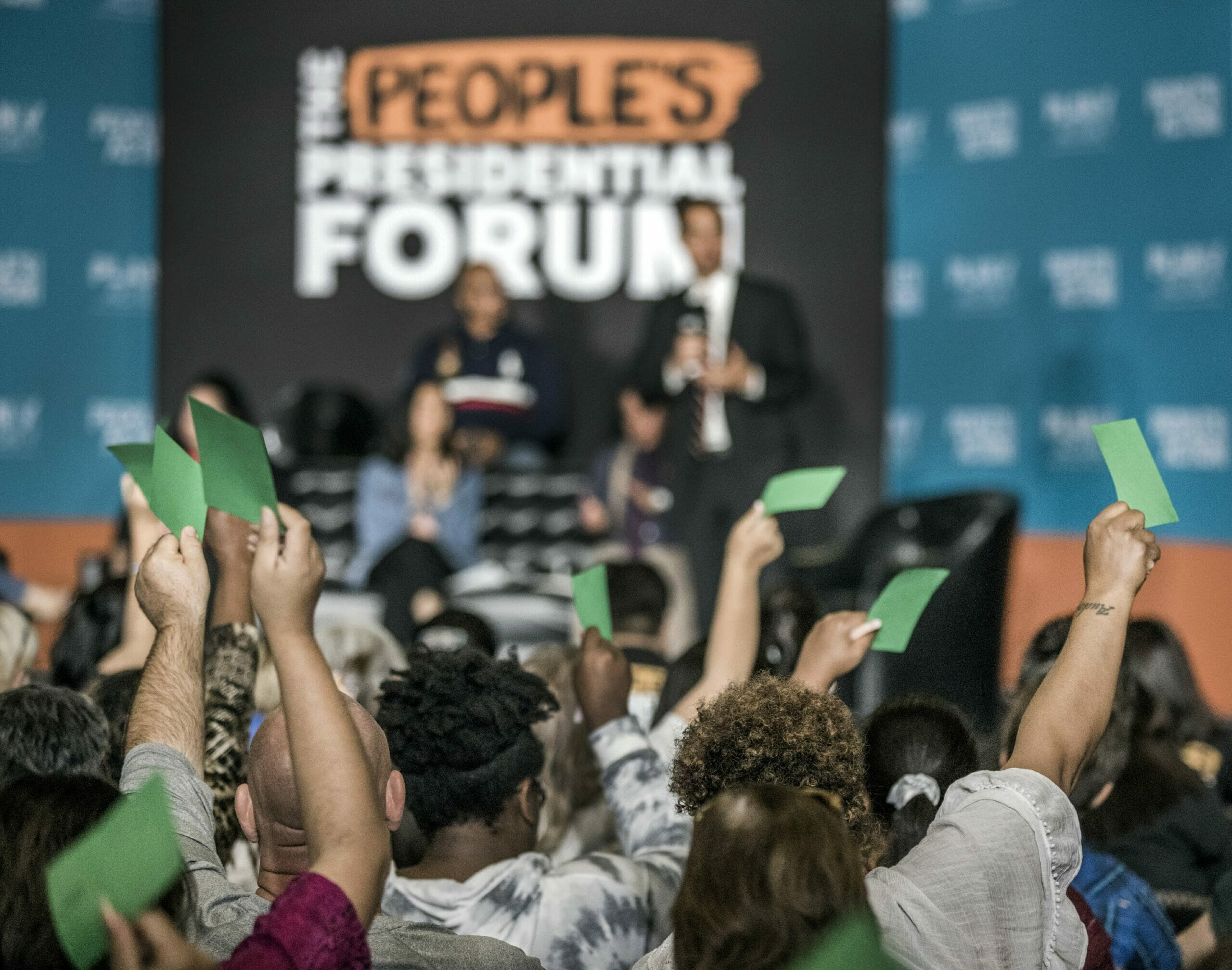 People wave green cards at a presidential forum