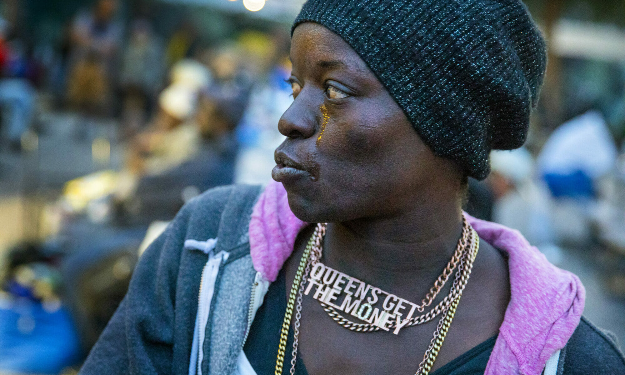 Kenya Obote wearing a light jacket, gold necklaces and a black scarf on her head