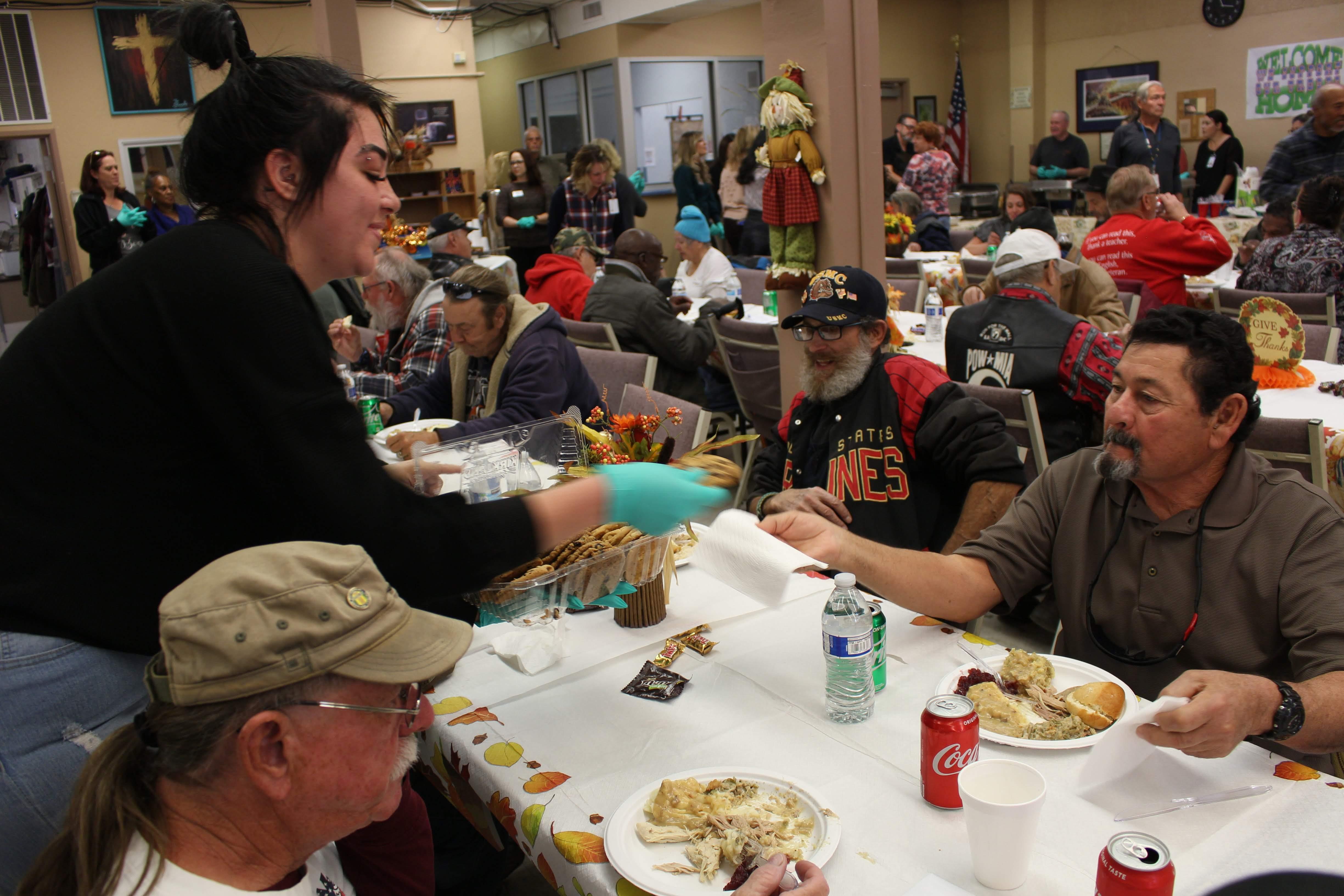 Volunteer gives cookies to veterans