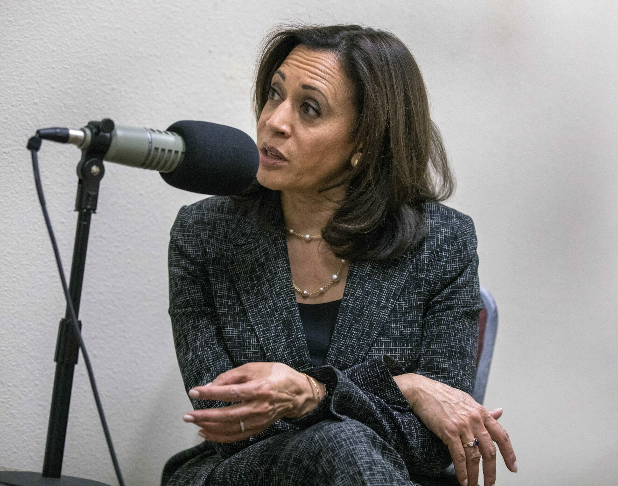 Kamala Harris in a grey suit seated at a microphone