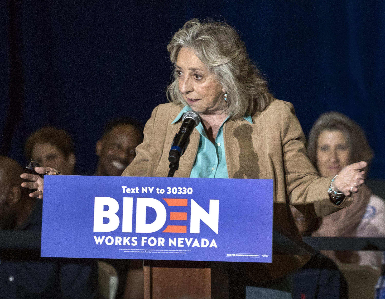 Dina Titus at a podium in a blue shirt and tan jacket