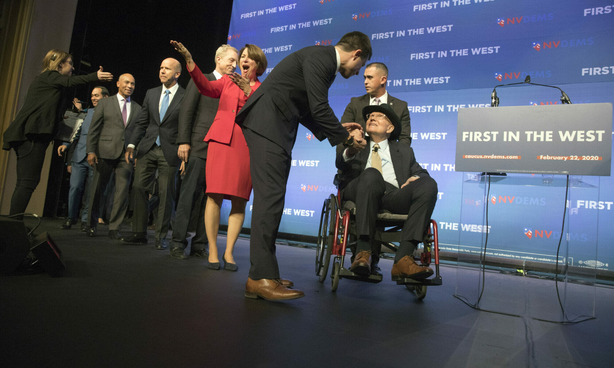 Harry Reid on stage in a wheelchair being greeted by candidates