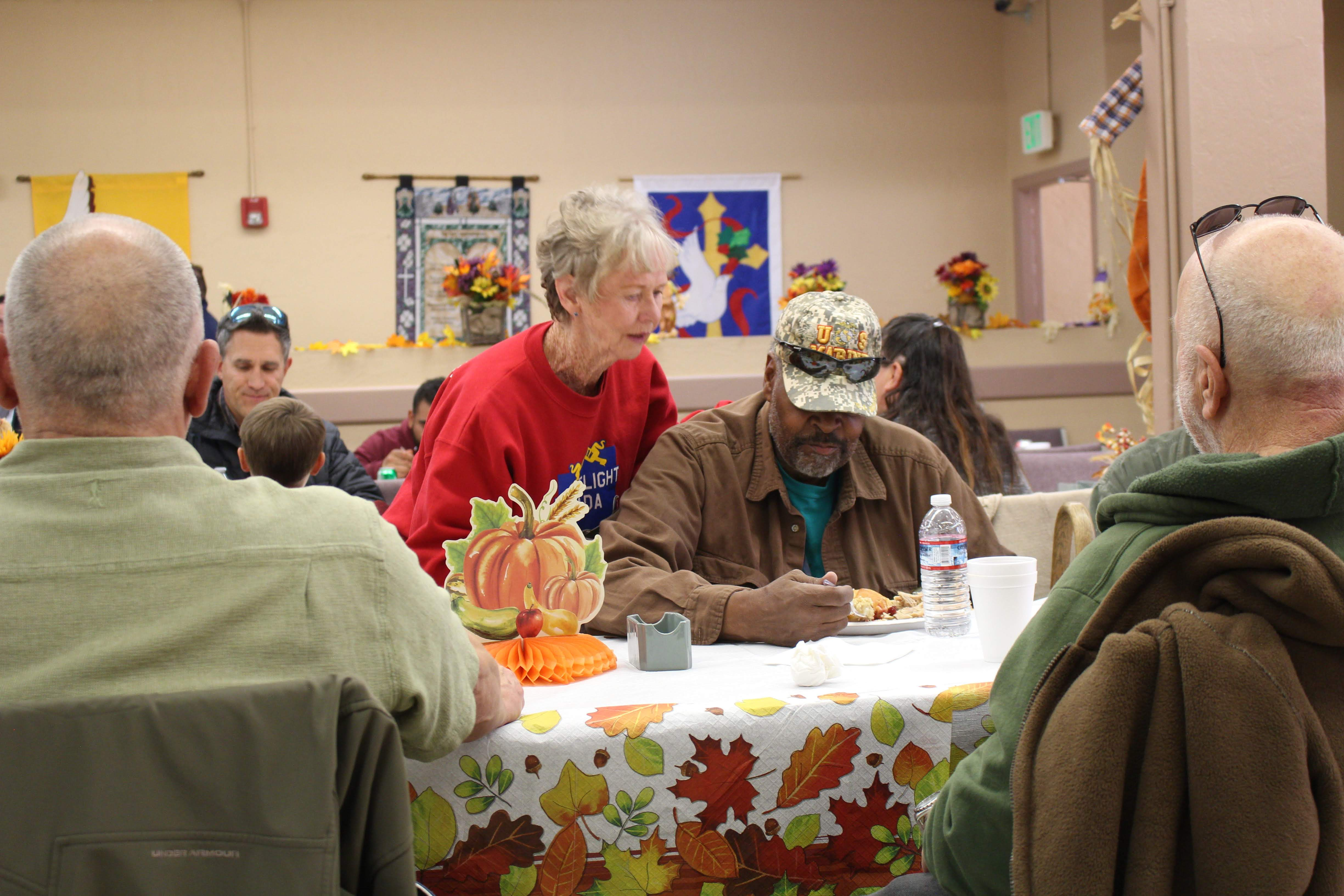 Volunteer talks with veteran at Thanksgiving meal