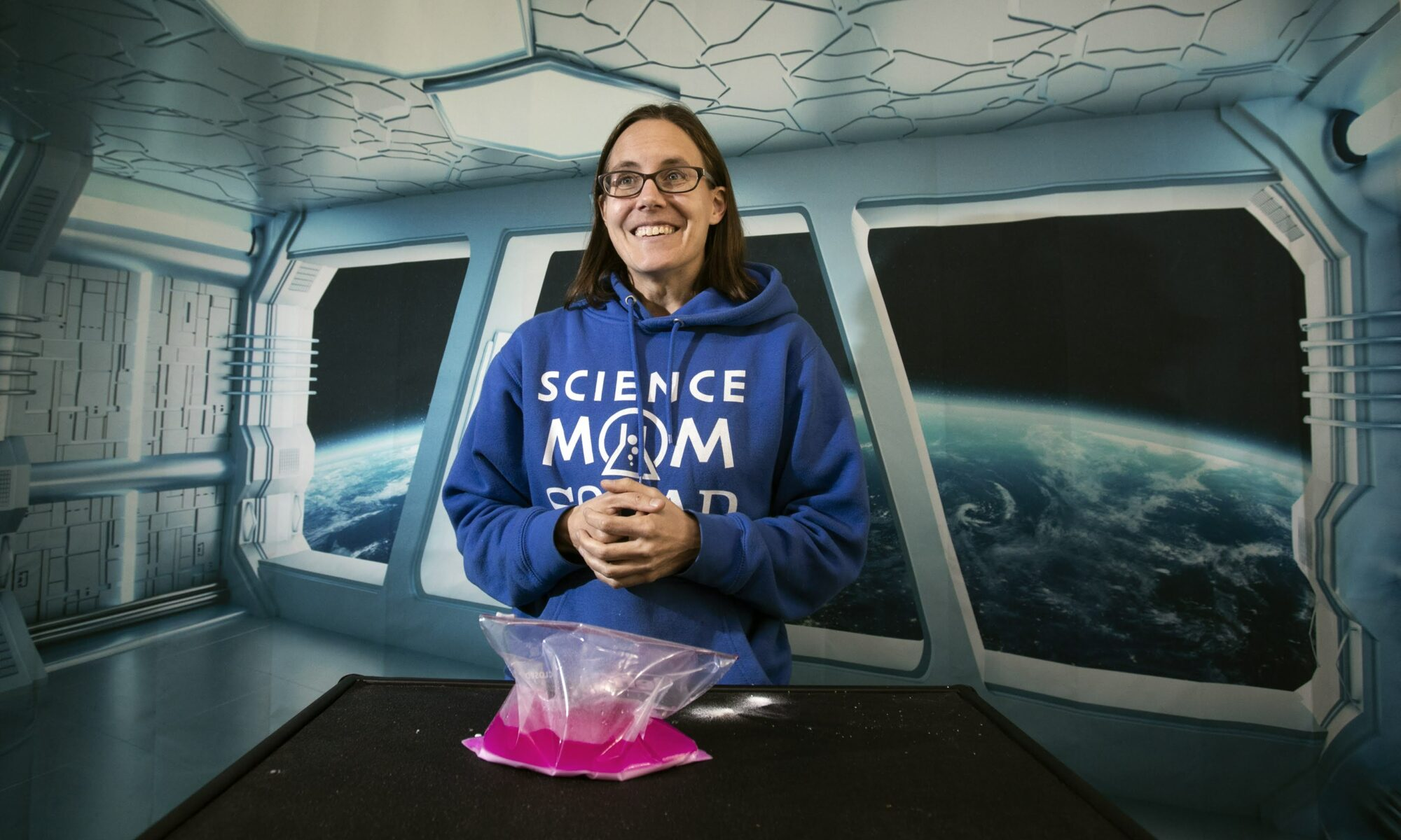 Jenny Ballif, in a blue science mom squad sweatshirt, standing in a space themed room