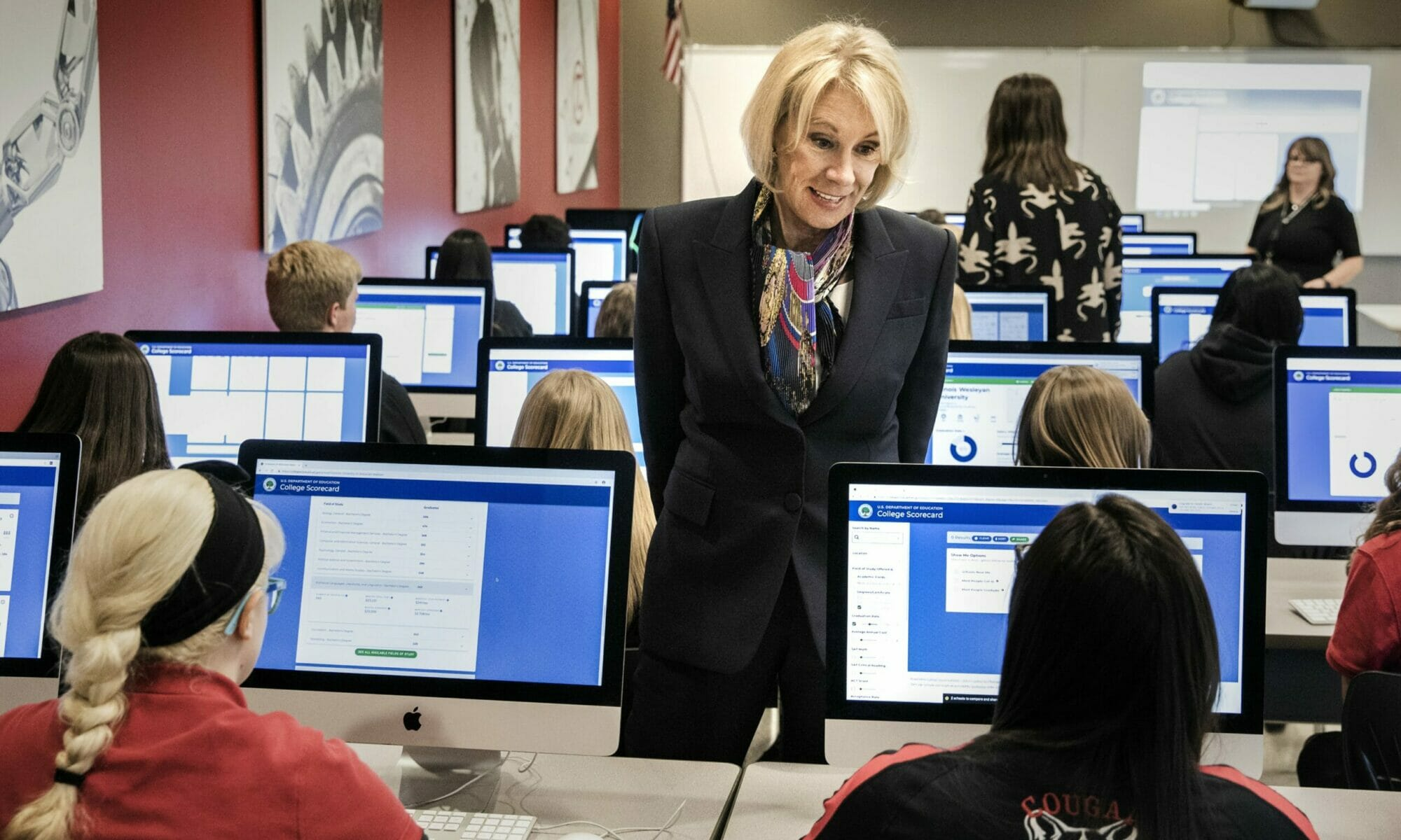 Betsy DeVos speaking with a student seated in front of a computer