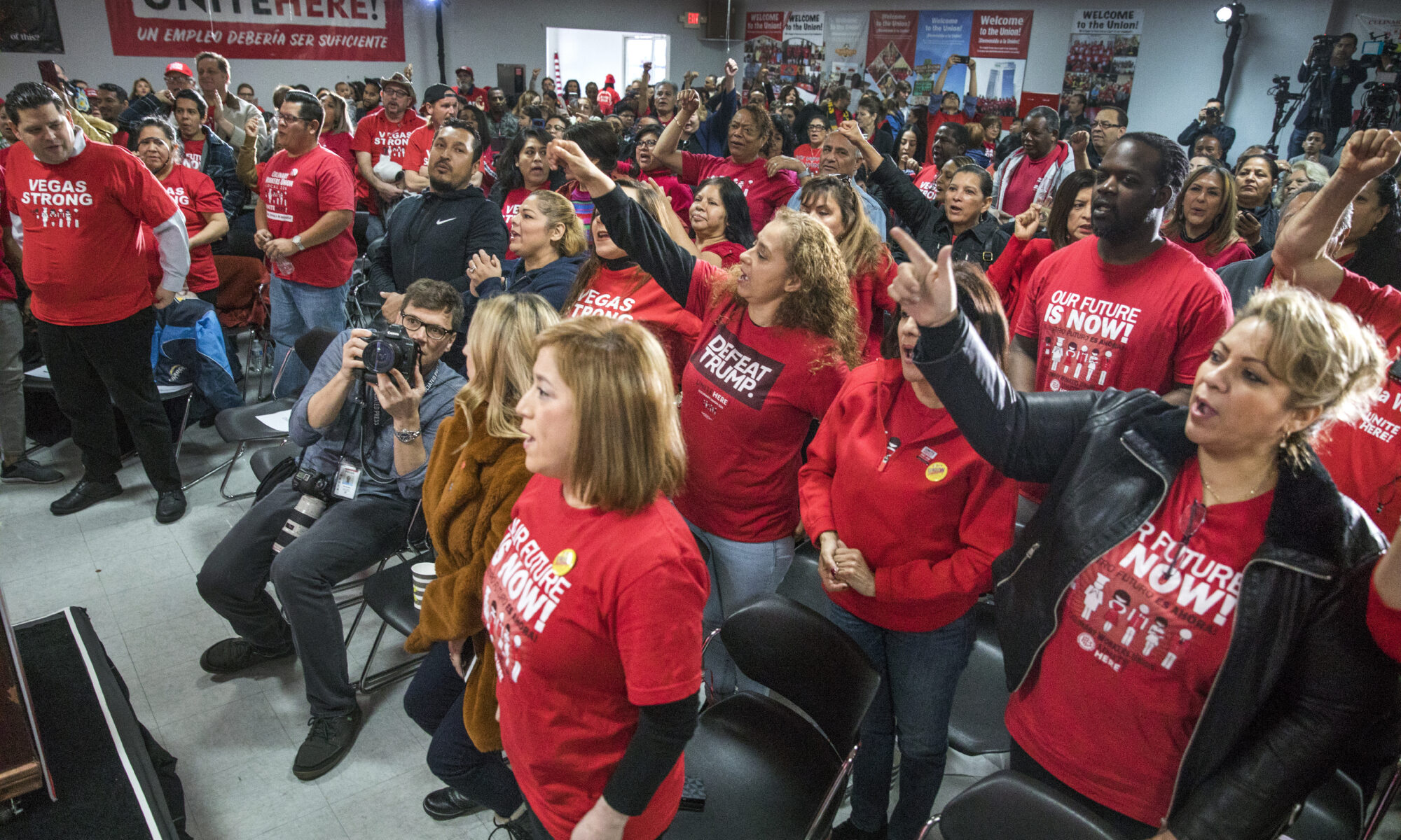 Union members in red shirts at a town hall event