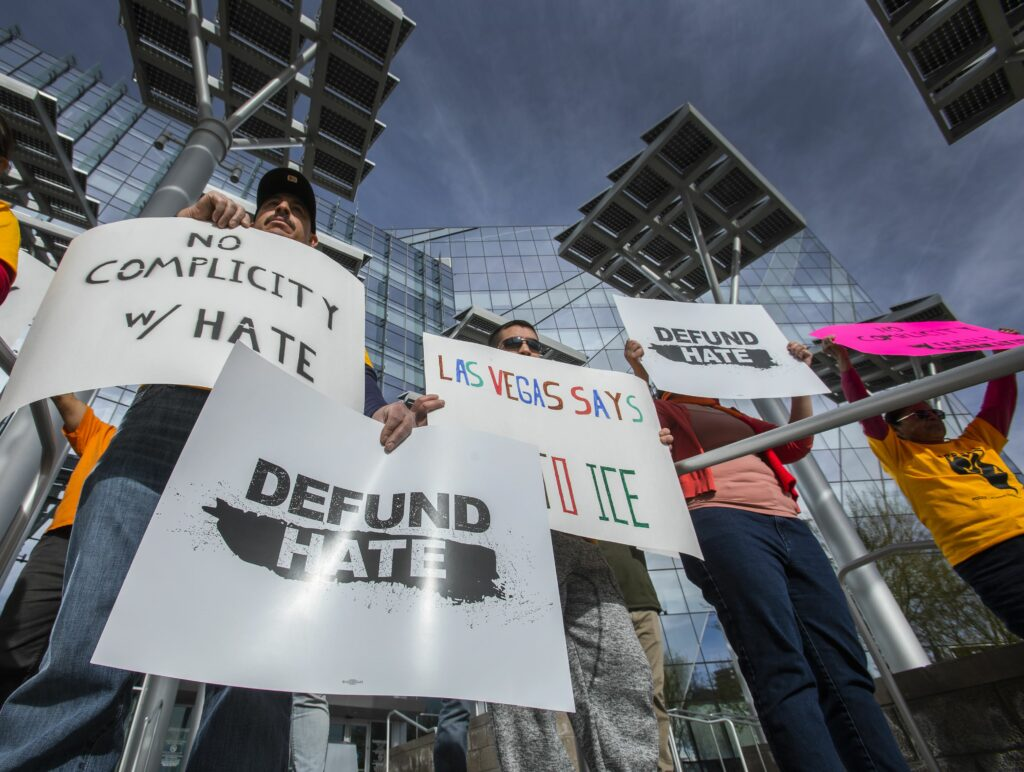People hold sign saying defund hate