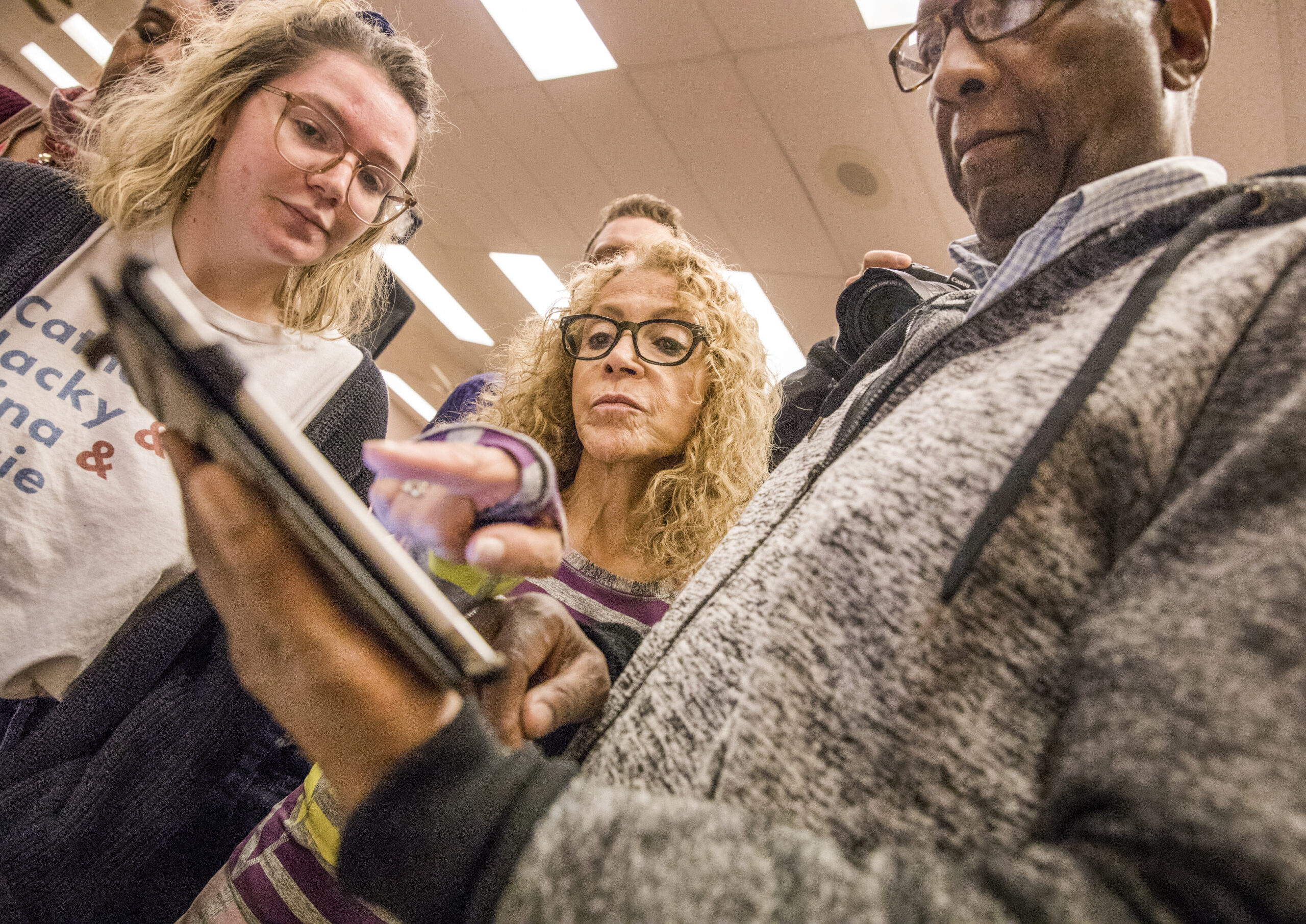 Digital director Emma Kraus, left, assists volunteers Diane and James Richmond during a caucus training