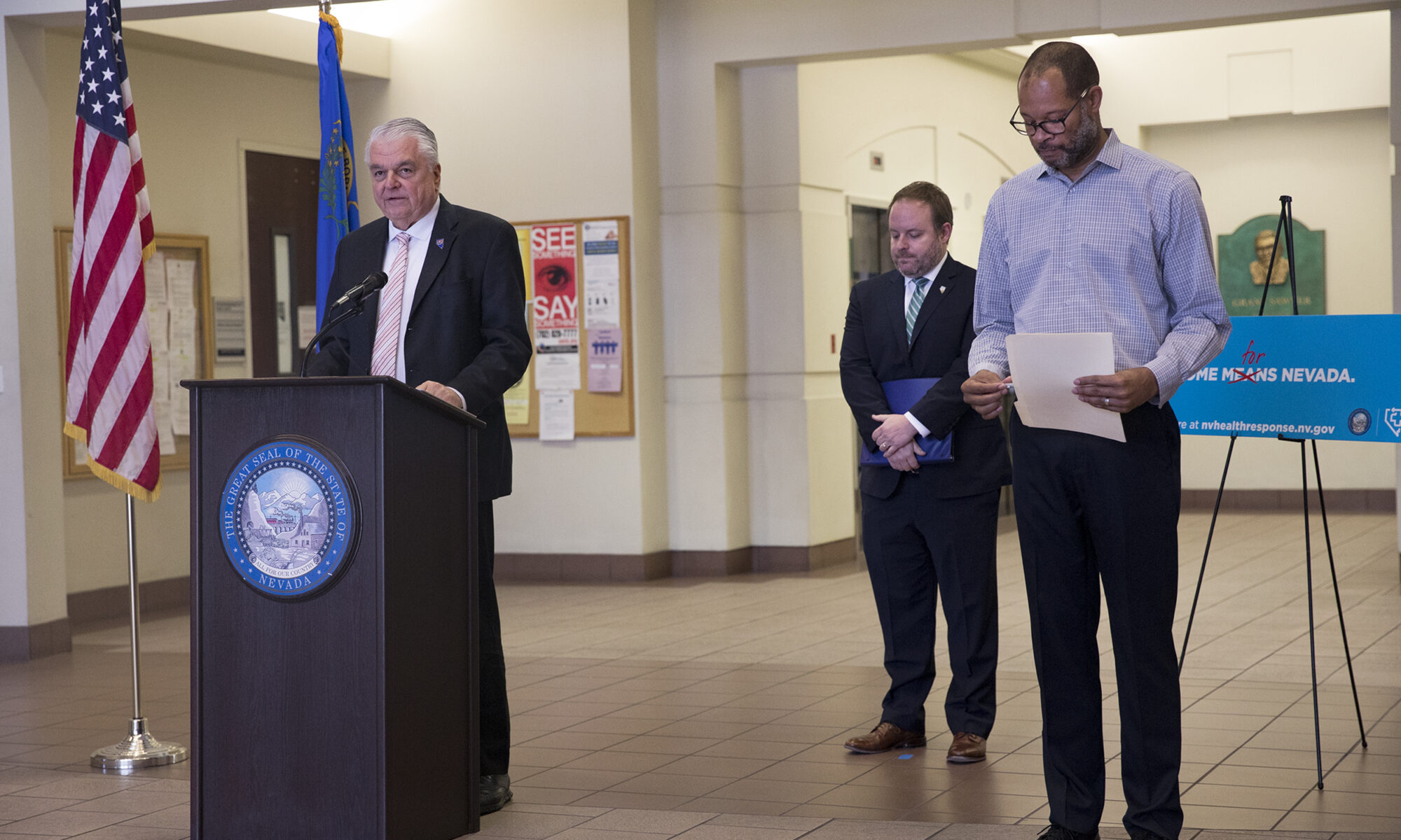Gov. Steve Sisolak stands behind a podium at a press conference, alongside Treasurer Zach Conine and Attorney General Aaron Ford.
