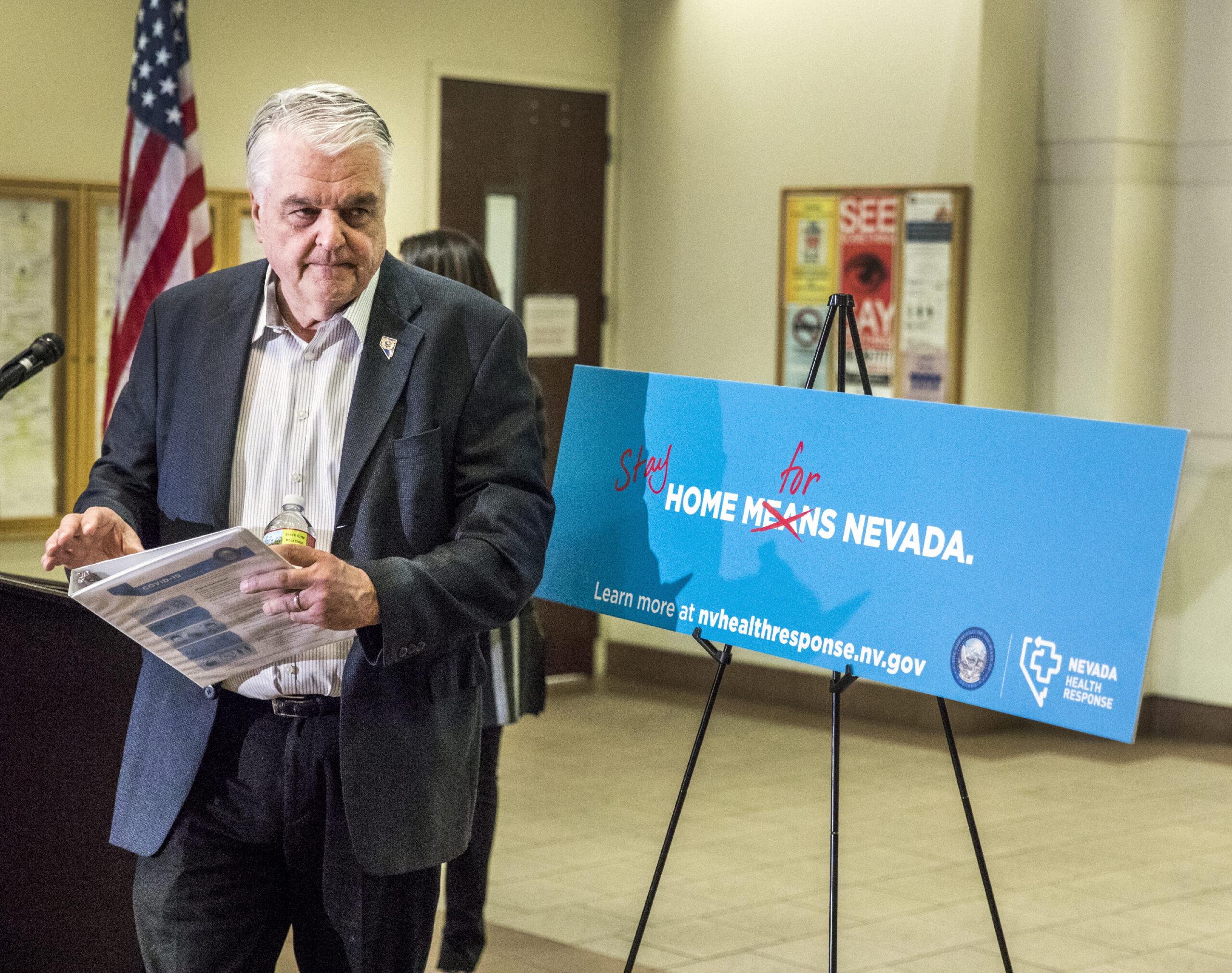 Steve Sisolak stands away from podium
