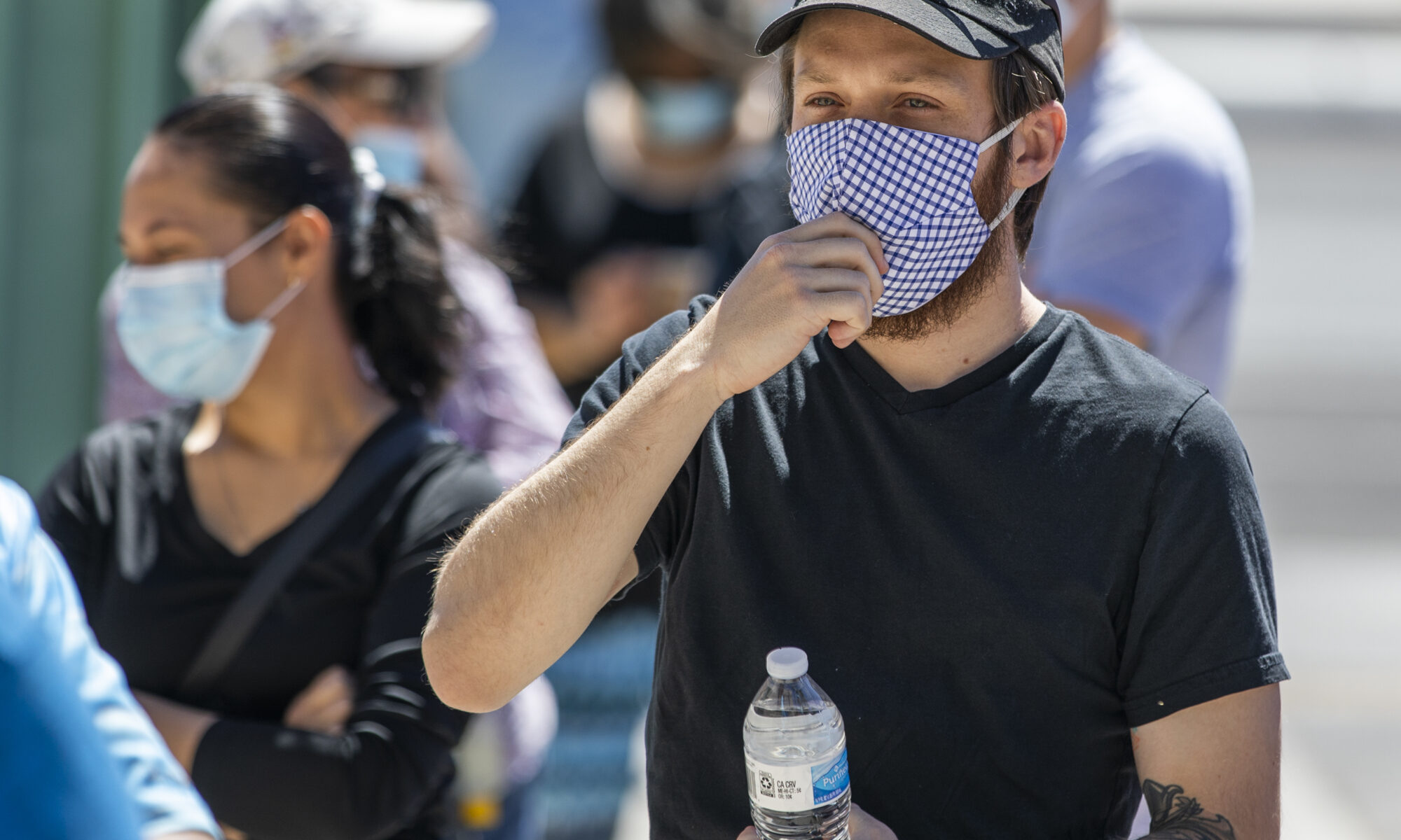 A man pulls at his mask in line