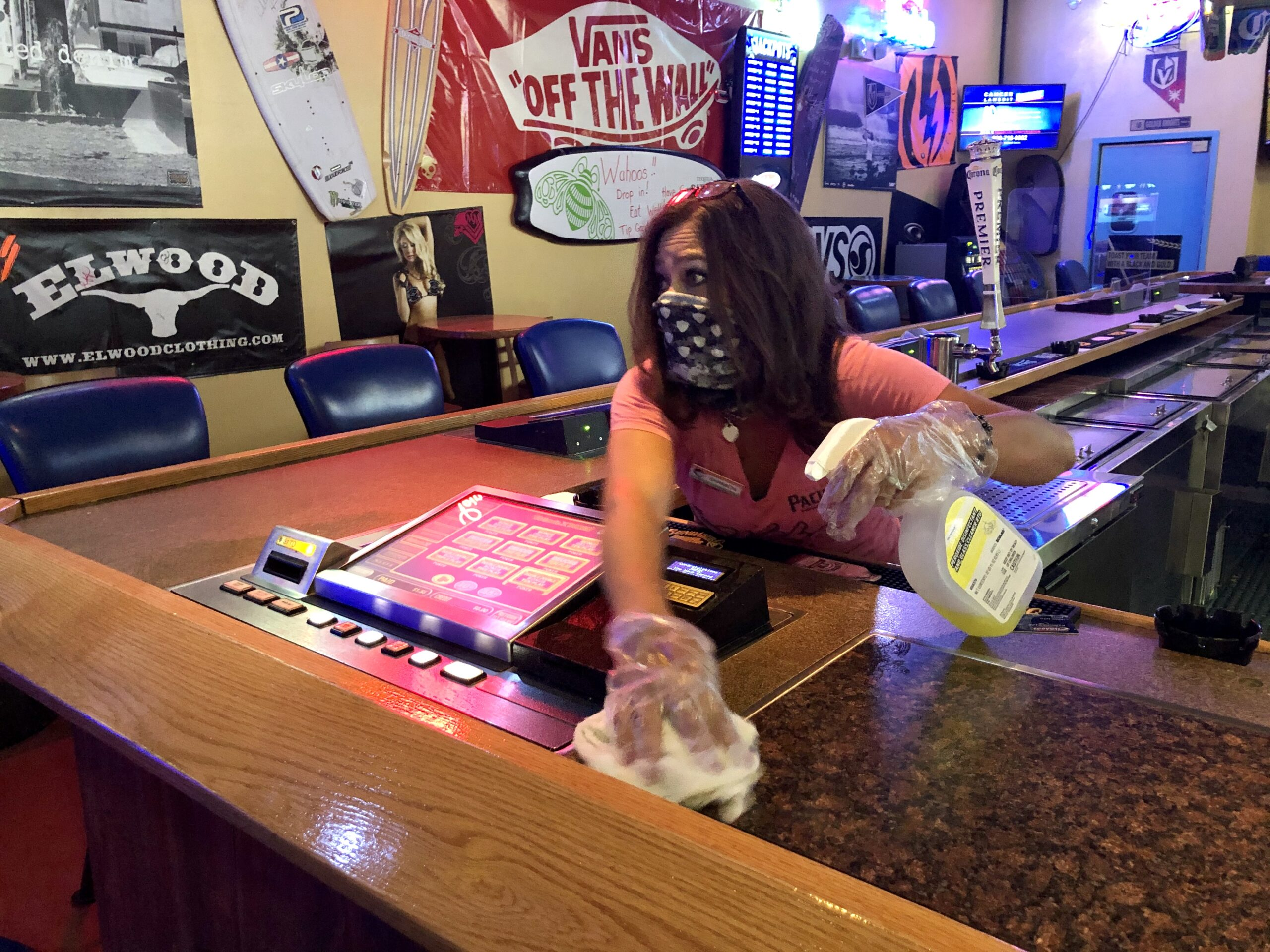 Wahoo's Fish Tacos bartender Shannon Dunmire cleans one of the Sunset Road and Rainbow Boulevard tavern's 15 slot machines after a customer ended a gaming session