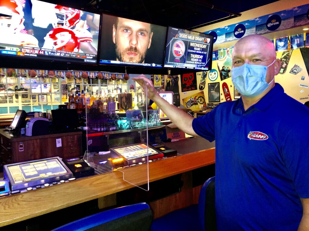 Wahoo's Fish Tacos owner Matt Flandermeyer shows off one of the plexiglass dividers between two bar top slot machines at his tavern on Sunset Road and Rainbow Boulevard.
