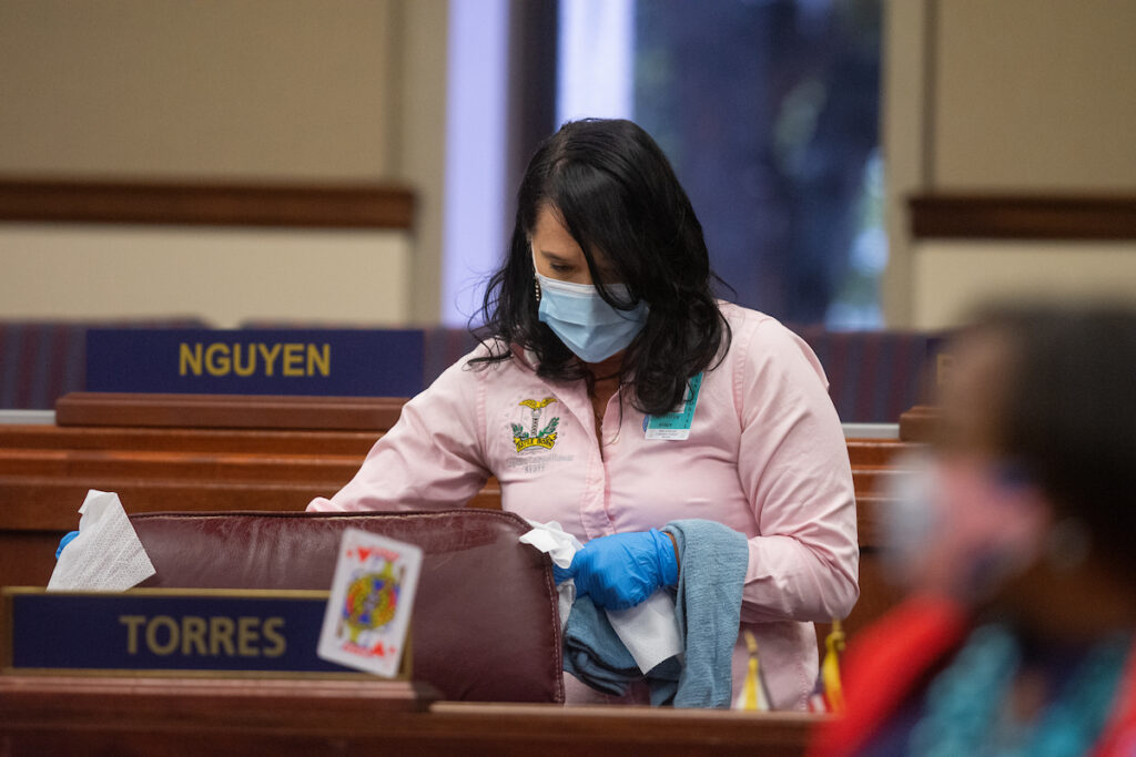 A member of the Legislative janitorial staff cleans inside the Assembly chambers on Friday, July 31, 2020 during the first day of the 32nd Special Session of the Legislature in Carson City.