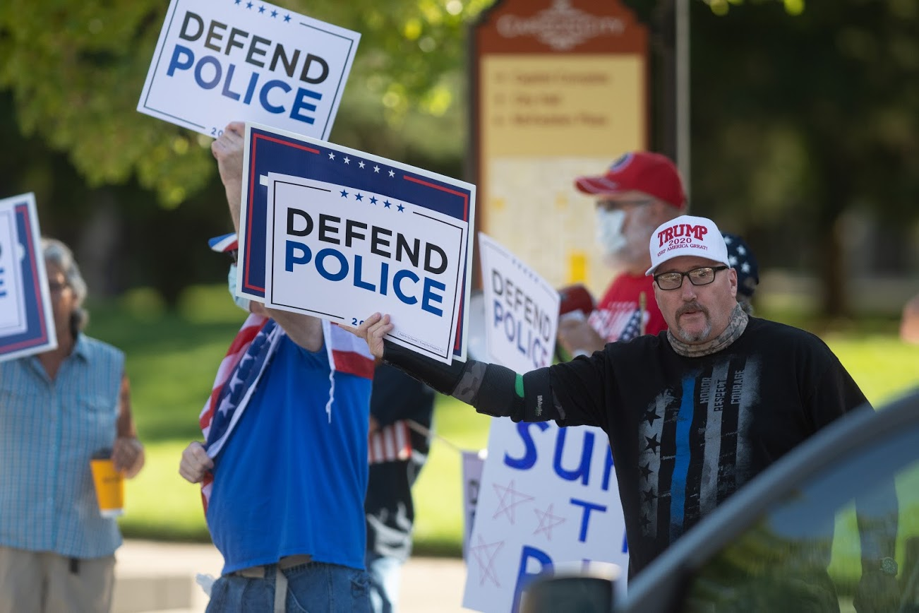 """A man wearing a Trump 2020 hat with a sign that says """"Defend Police"""""""