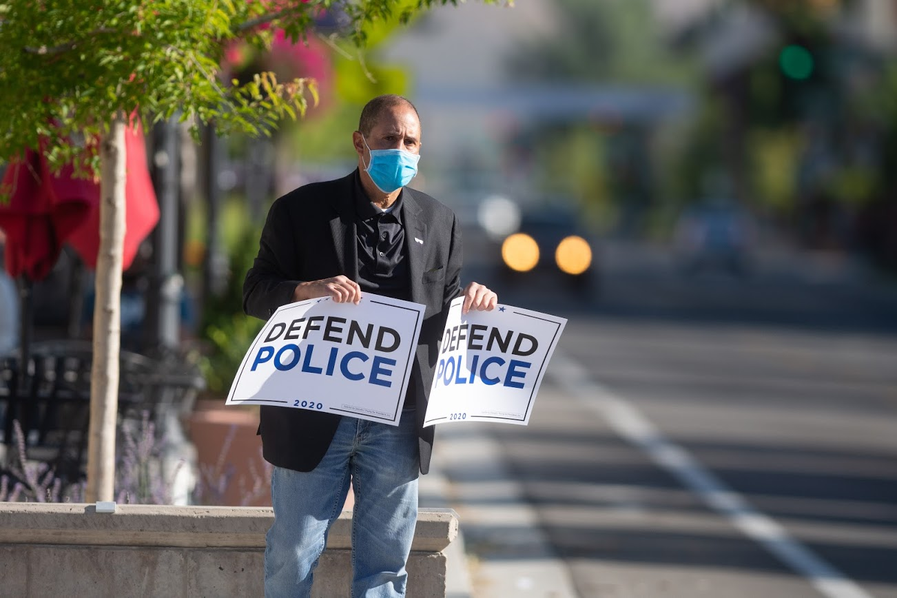 """A man holding signs says """"Defend Police"""""""
