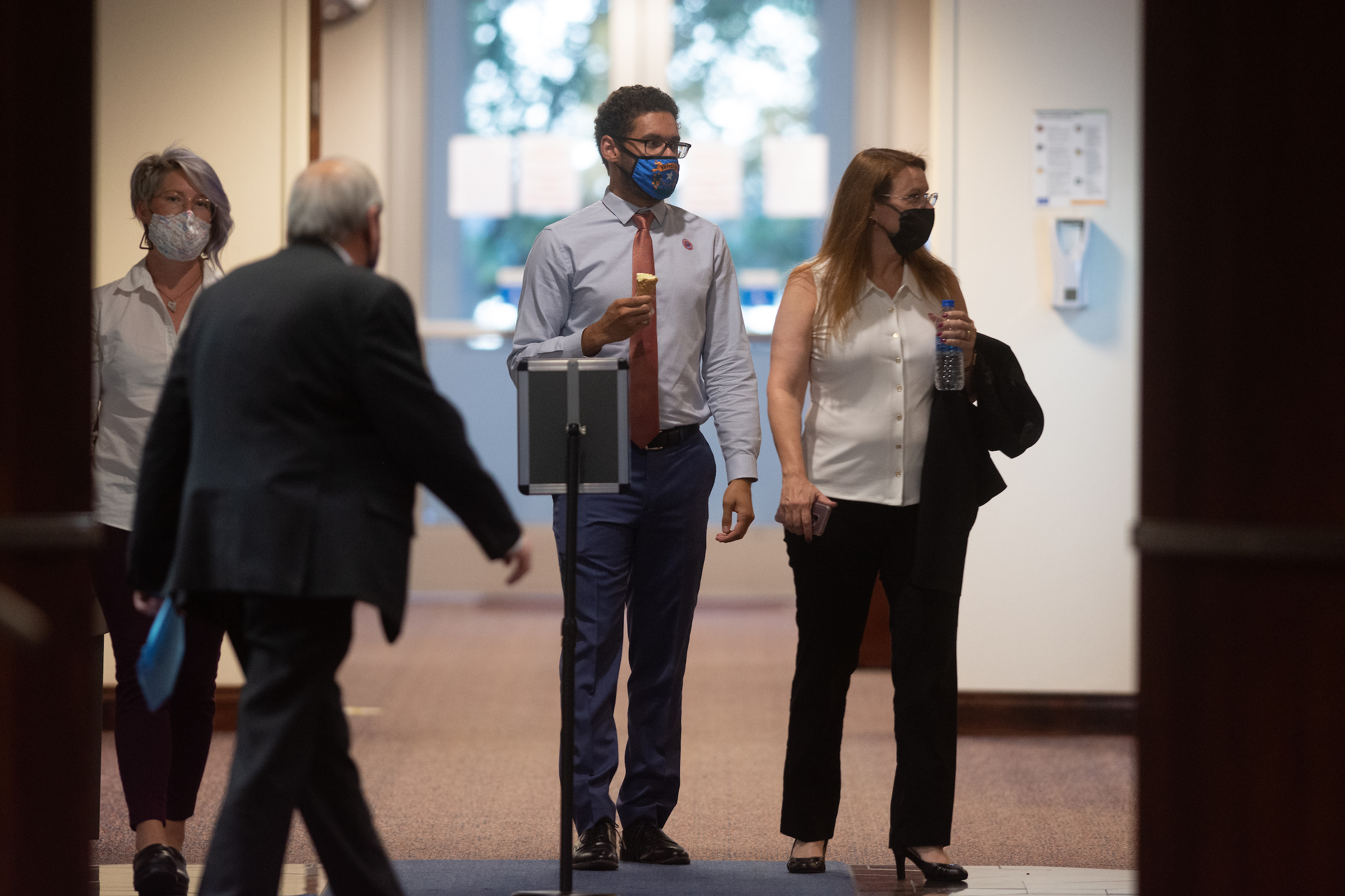 Assembly members Sarah Peters, Howard Watts II and Michelle Gorelow walking in a hallway in the Legislature Building