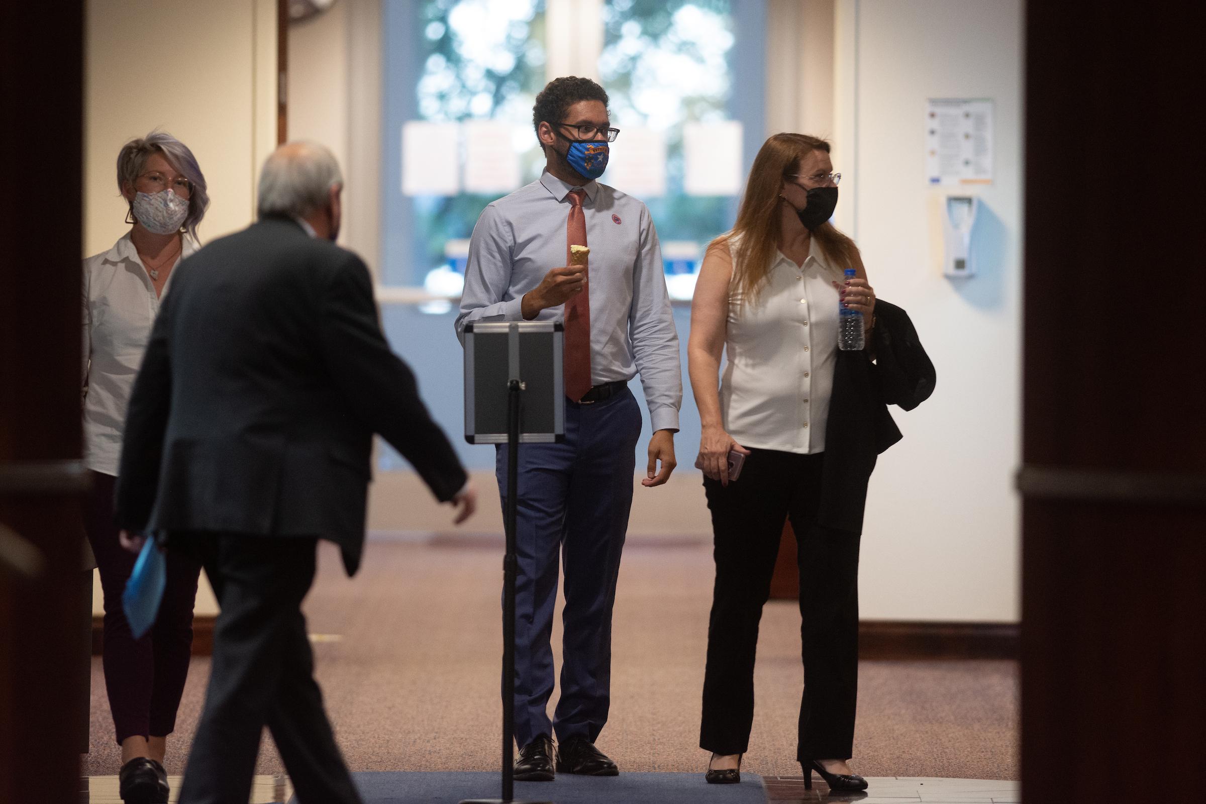 Assembly members Sarah Peters, Howard Watts II and Michelle Gorelow walking in a hallway in the Legislature Building