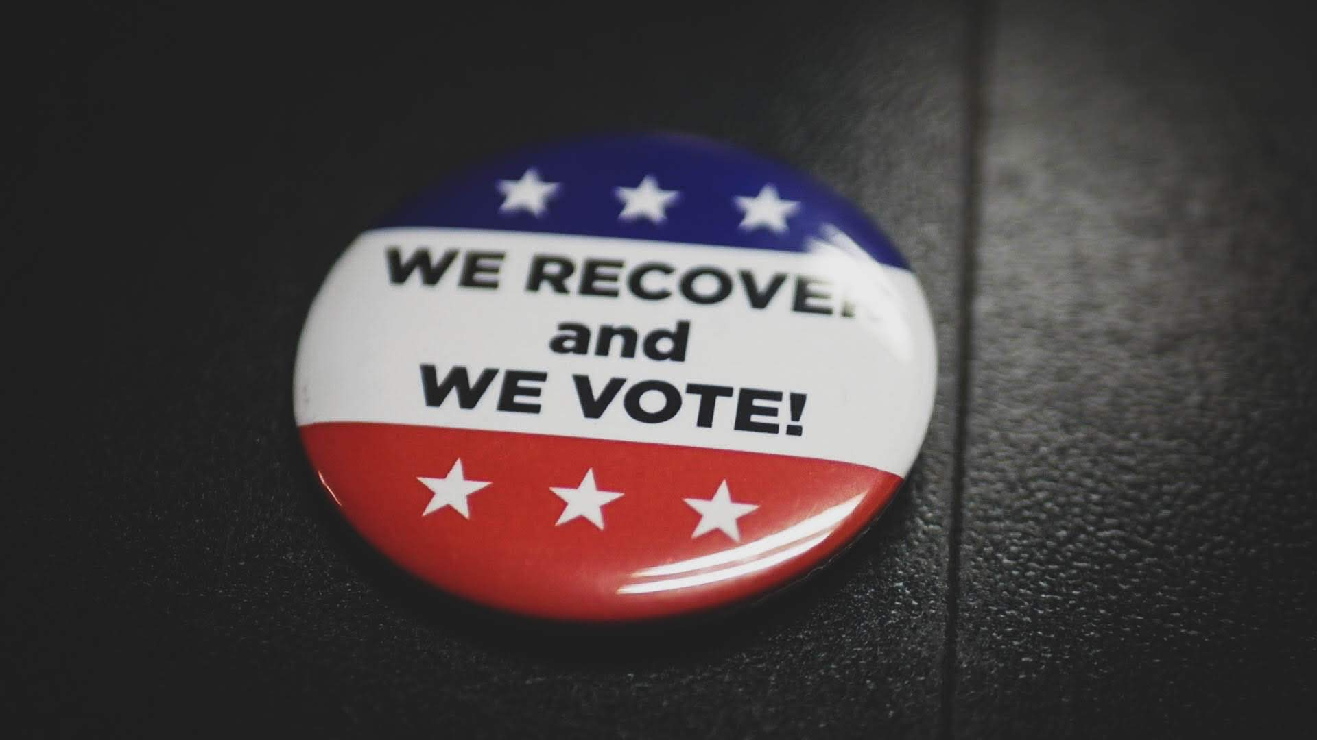 """A pin that reads """"We recover and we vote!"""""""