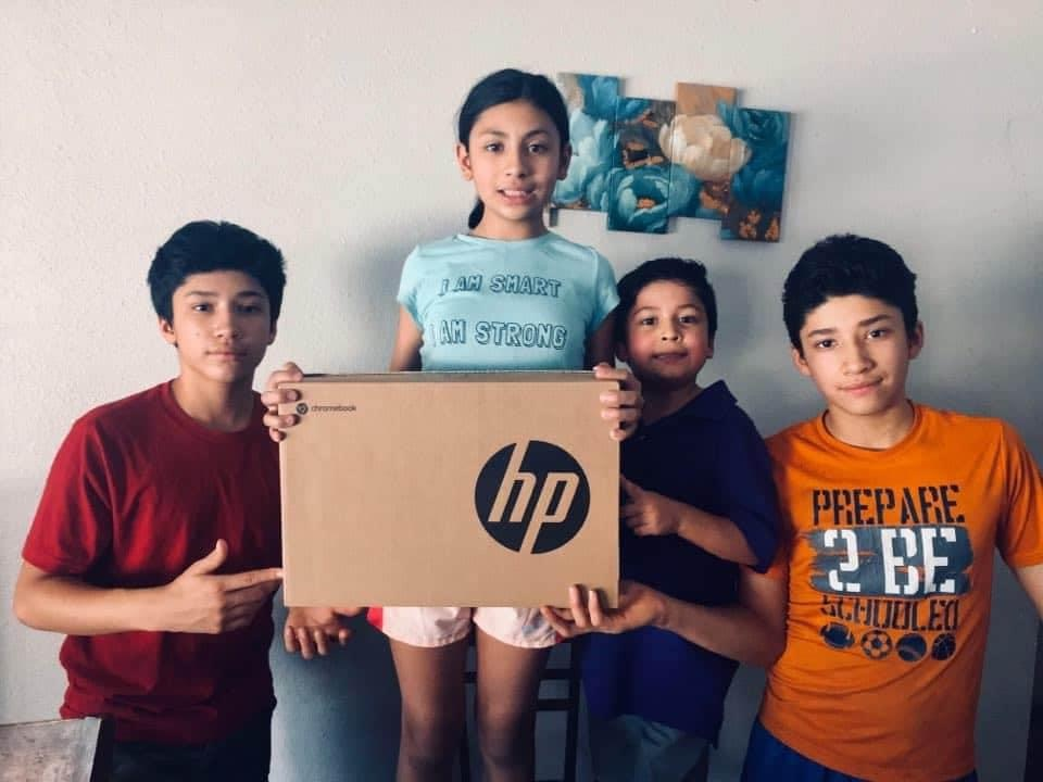 Camila Flores, 11, and her brothers clutch a new laptop that was donated to their family ahead of the upcoming school year.