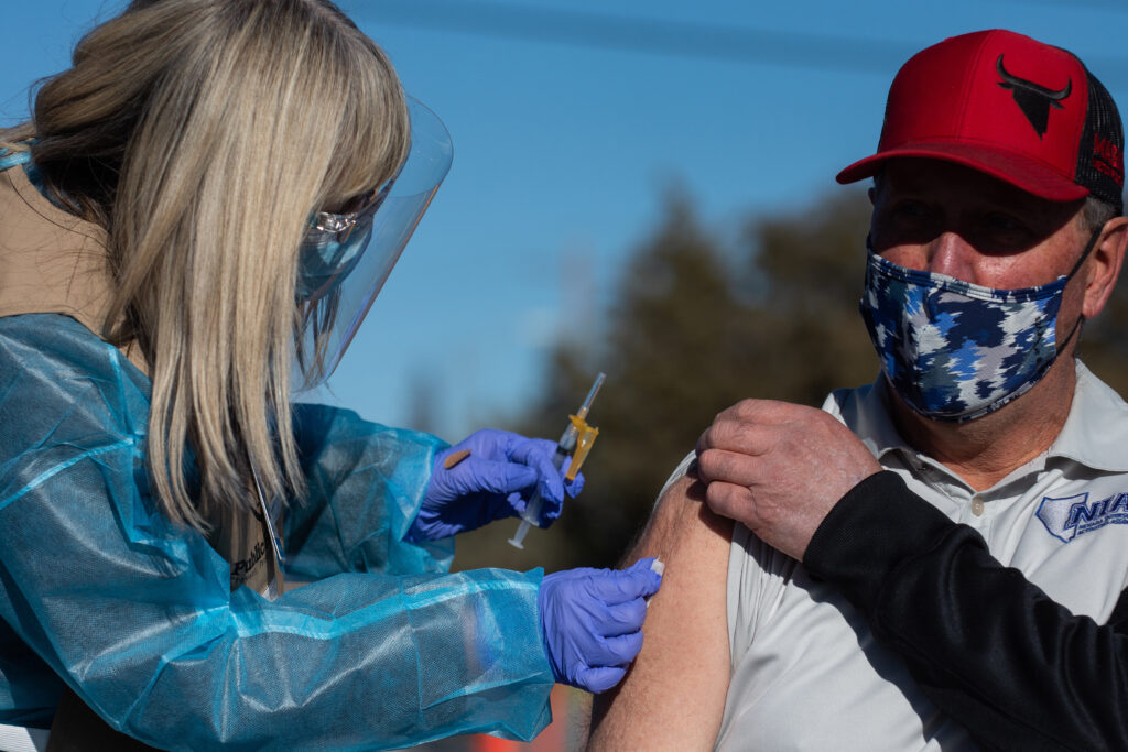 A man's arm is cleaned before receiving a vaccination.