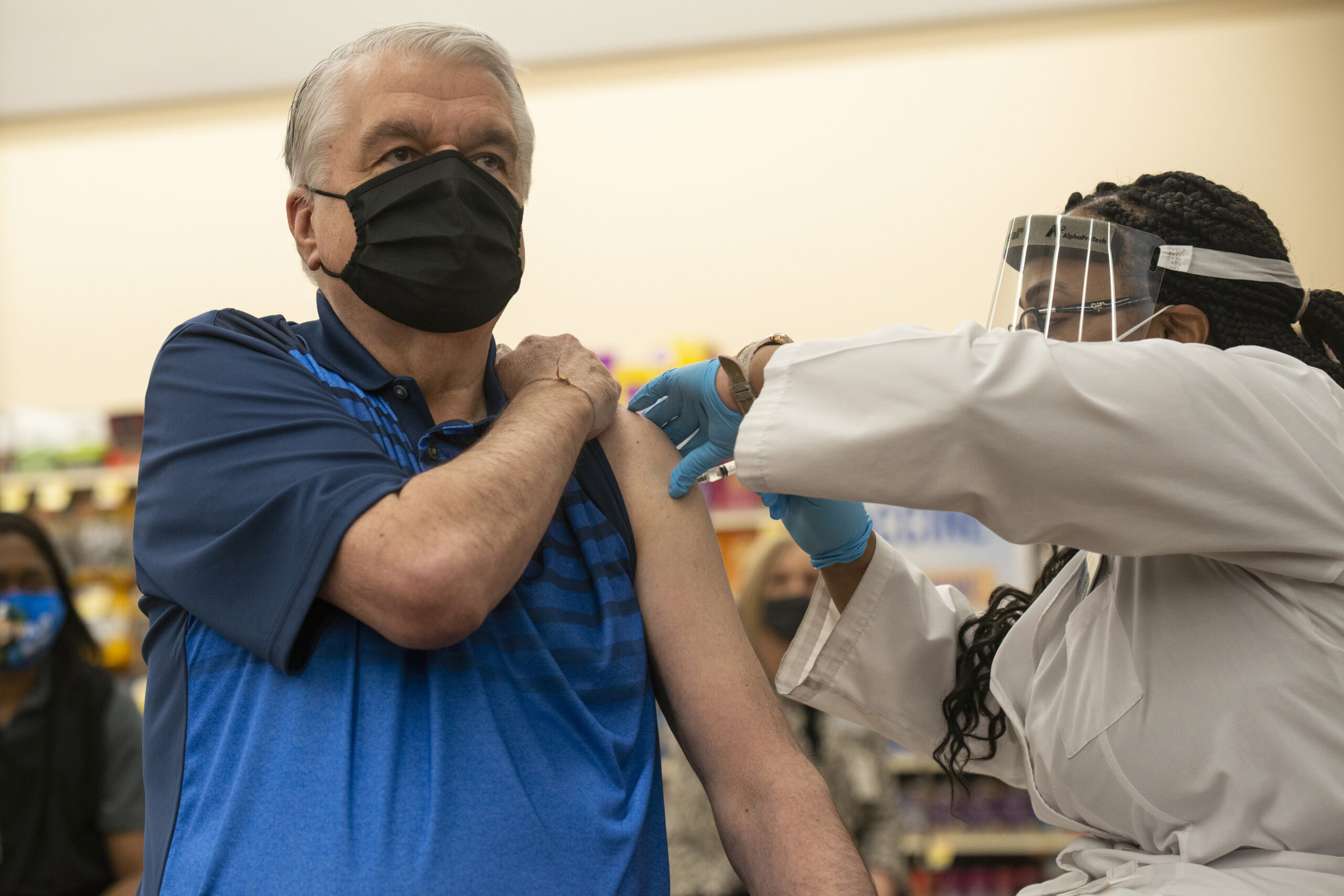 Steve Sisolak receives the COVID-19 vaccine from an Albertsons pharmacist