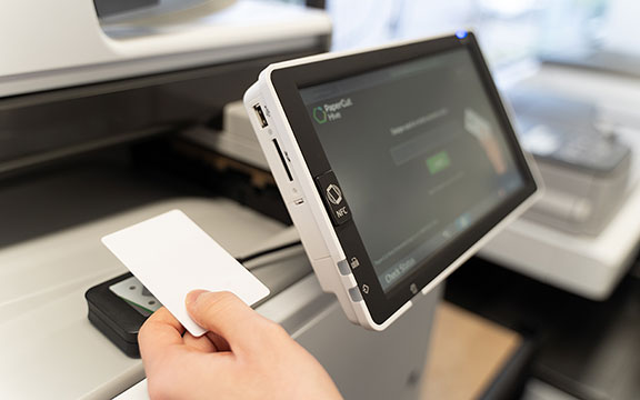 A photo of someone`s hand touching their office access card to a card reader that is connected to a Multi Functional Printer in order to release securely a printed document