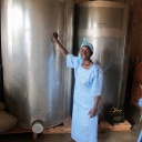 A farmer from Mbeere, Kenya, stands by two metal silos. The silos allow her to store grain for use by her family, and to sell. Photo credit: W. Ojanji/CIMMYT