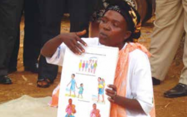A woman in Burundi teaches optimal practices for children's health using a poster, part of the Tubaramure (let's help them grow) program. Behavior change communication is a critical pathway for improving health and nutrition practices. Photo by Megan Parker