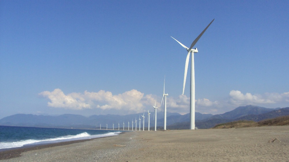 "Bangui Windmills are located in Bangui, Ilocos Norte, Philippines. It is also known as the NorthWind Bangui Bay Project, a project by the NorthWind Development Corporation as a practice renewable energy sources and to help reduce the greenhouse gases that cause global warming. The project is the first ""Wind Farm"" in the Philippines consisting of wind turbines on-shore facing the South China Sea and considered to be the biggest in Southeast Asia. The project sells electricity to the Ilocos Norte Electric Cooperative (INEC) and provides 40% of the power requirements of Ilocos Norte via Transco Laoag. (Photo credit: Paolo Dala)"