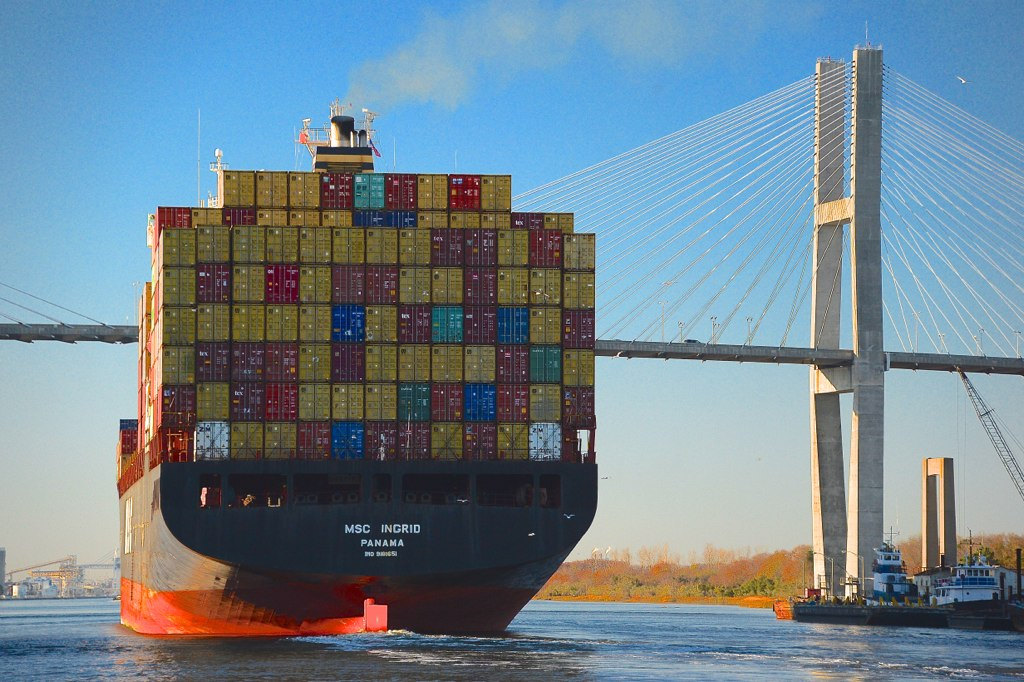 A huge container ship sails under the bridge from Savannah, Georgia into South Carolina, as it prepares to unload its cargo imported from the far east.