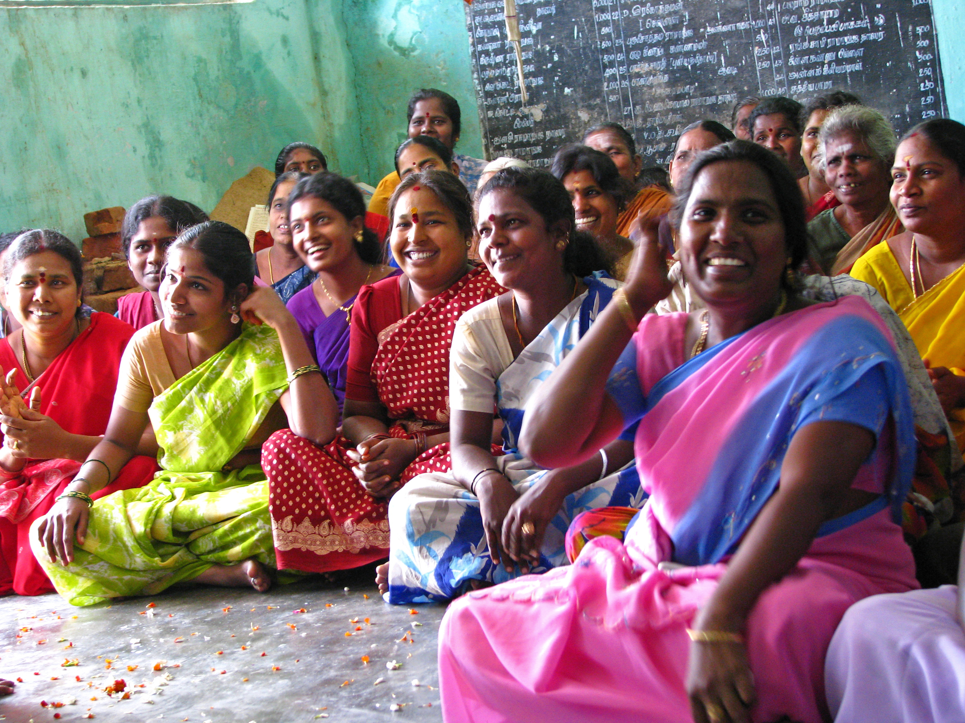 Rural women in their richly coloured saris meeting as members of self-help groups (SHGs).
