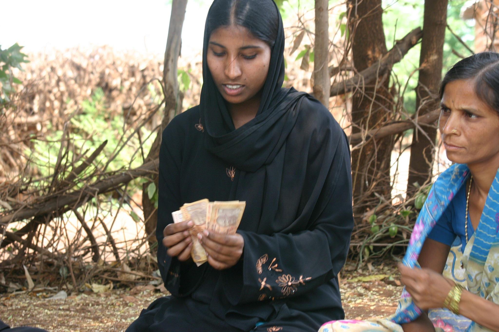A woman counting money at a Self Help Group Meeting in Bidar, Karnataka