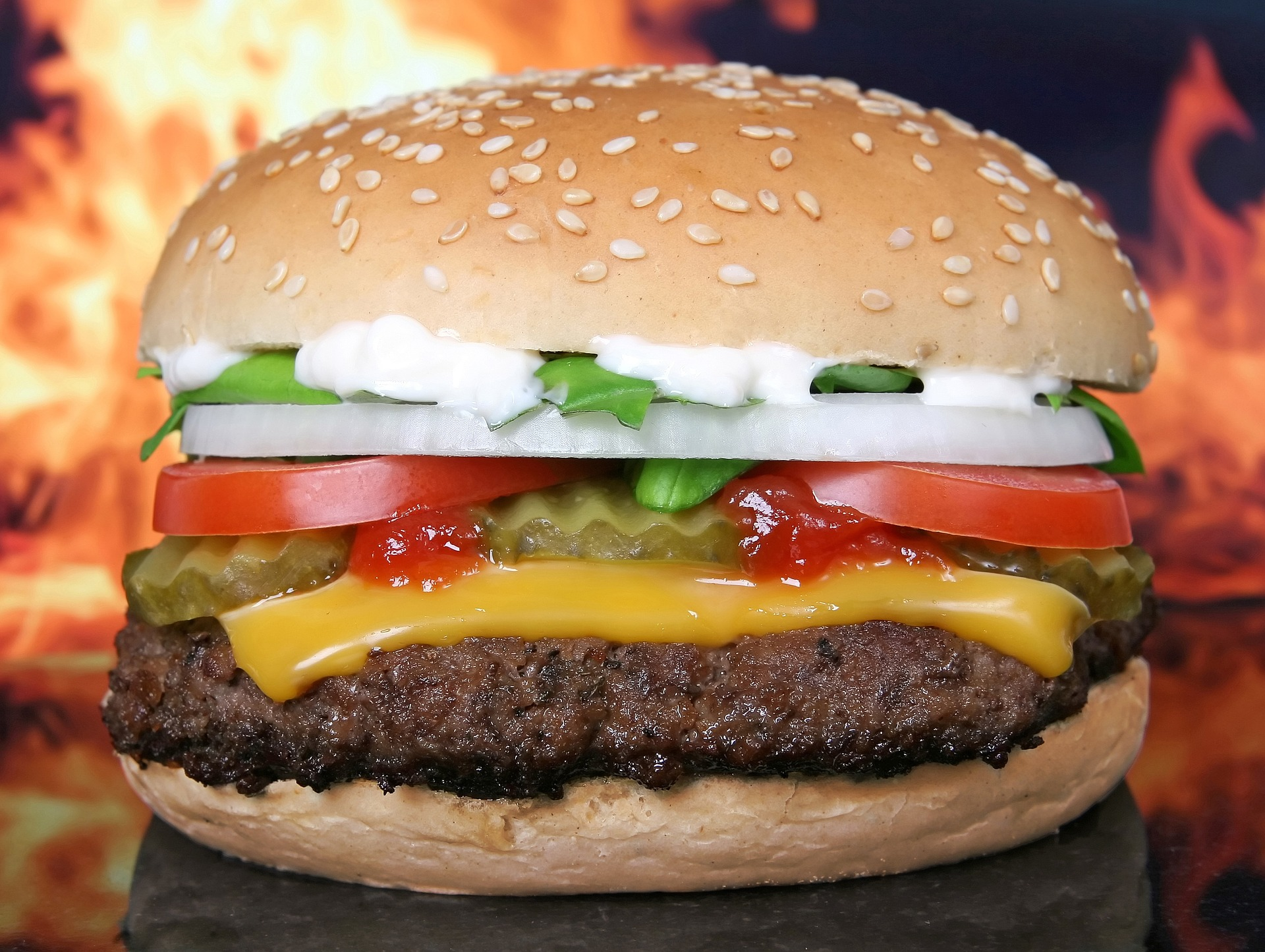 Hamburger in front of flames, McDonald's, KFC, Burger King, Domino's are being asked by investors to curb their carbon emissions and water usage across their supply chains