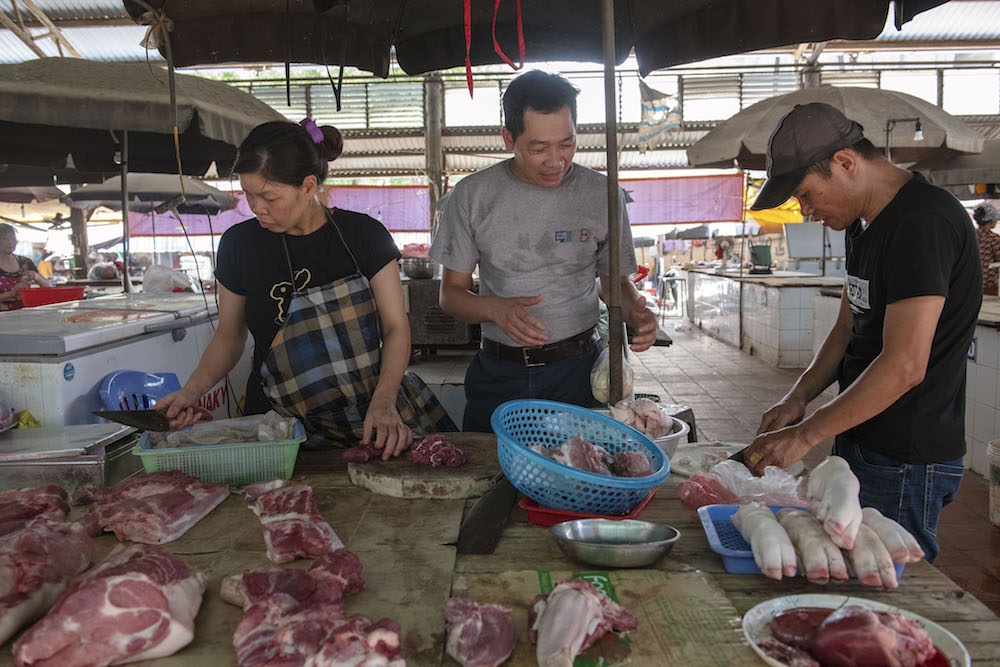 Speaking with pork traders at the market. Photo by C. De Bode/CGIAR