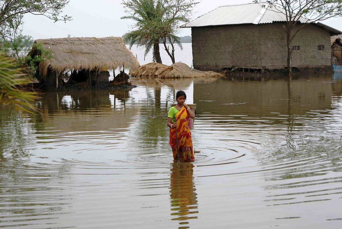 Flood Waters and Daily life – a lady trying to reach home. Photo: Anil Gulati – India Water Portal