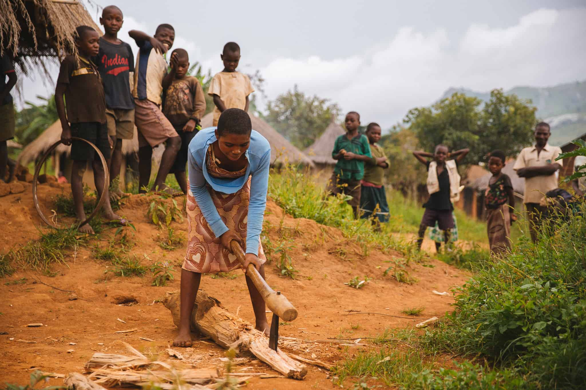 Young Women Chopping Wood as Group of Boys Watch, Malawi